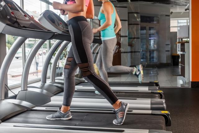 スポーツジムでランニングマシーンを走る二人の女性の画像