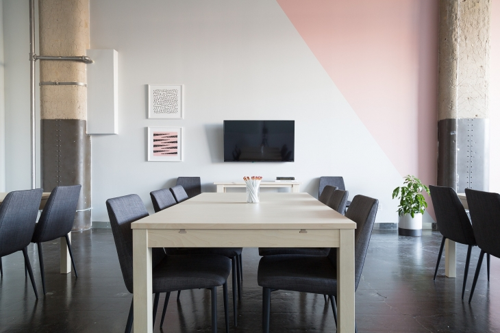 オフィス内にあるテーブル、いす、モニター、文具、観葉植物の写真