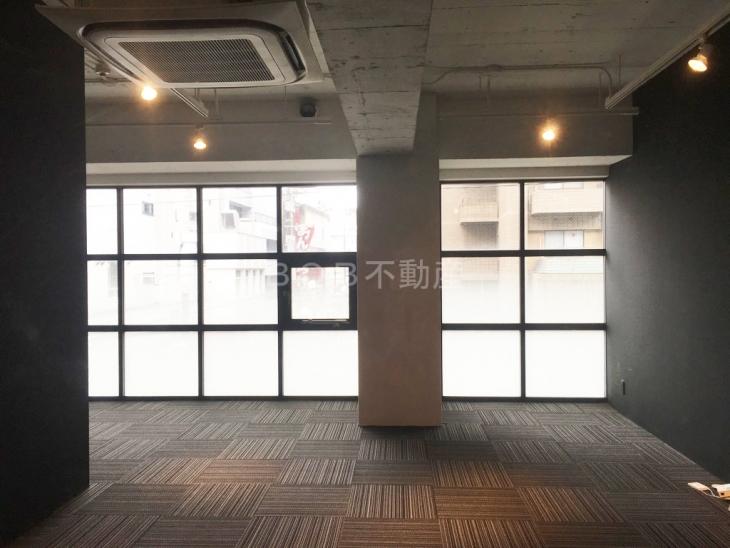 コンクリート打ちっぱなしの天井とモダンな店内の画像
