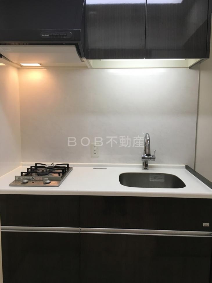 黒色のキッチンパネルをしたキッチンの画像