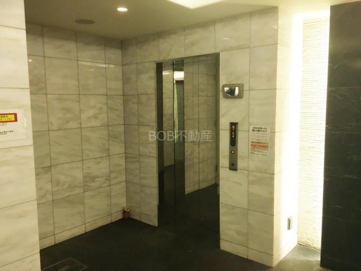 大理石調のエレベータホールの壁とエレベーターの画像