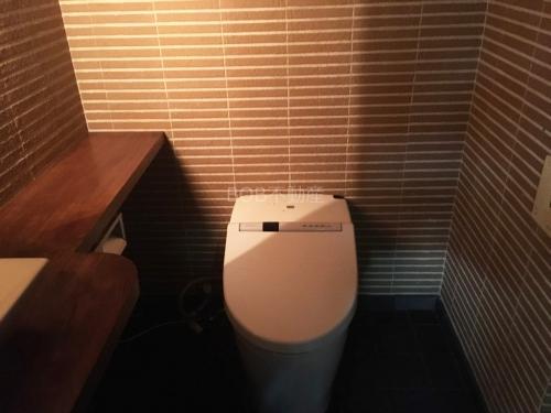 温水洗浄便座とタイル調のトイレ内の画像