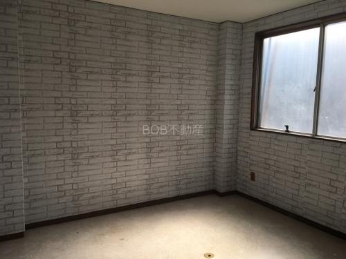 白いレンガ調の壁と白い床の内装の画像