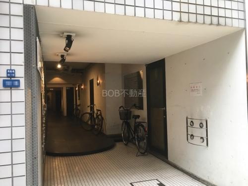 白い壁の建物入口と廊下に自転車が映る画像