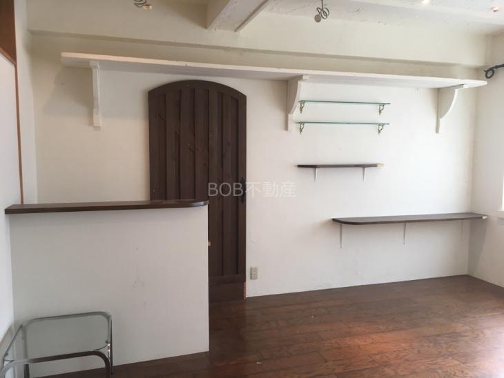 白い内装と茶色のフローリング、棚の画像
