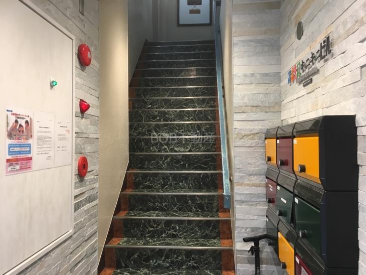 キレイにリフォームされた緑色の共用階段の画像