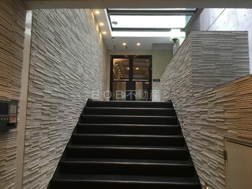 白いタイル張りの壁面と階段、入り口ドアが映る画像