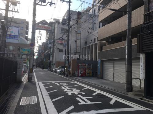 停止禁止と書かれた道路と茶色のタイル張りのマンションの外観画像