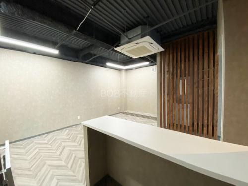 白い受付カウンターと白い内装と鉄骨がむき出しの天井が映った画像