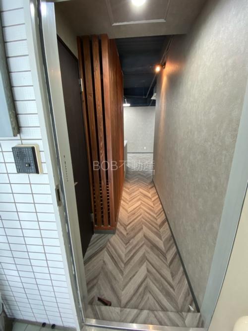 インターホンとお洒落な床材と木材と白い壁の写った画像