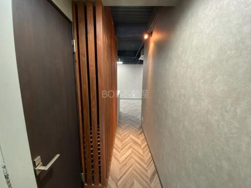 お洒落な床材と木材と白い壁、トイレのドアが写った画像