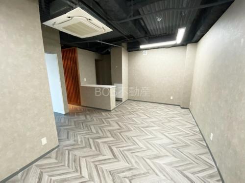 白い受付カウンターと白い床、白い内装、エアコンと黒い天井が映った画像