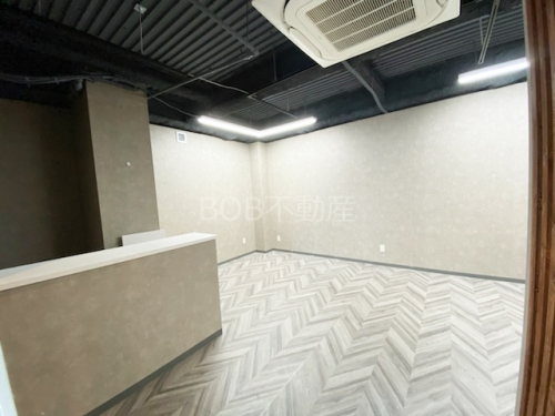 白い受付カウンターと白い床、白い内装、エアコンと黒い天井が映った画像3