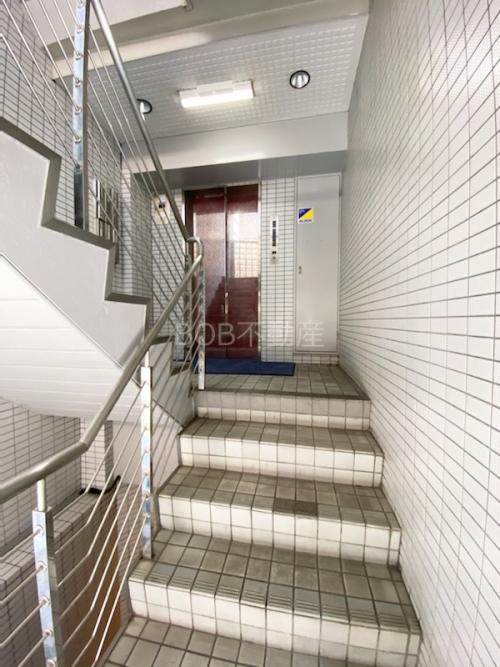 白いタイル壁と階段、奥にエレベーターが映った画像