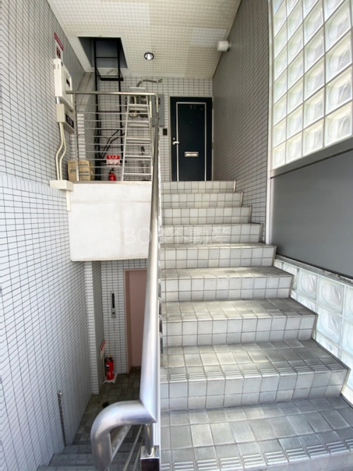 白いタイル壁と階段、奥に紺色の玄関ドアが映った画像