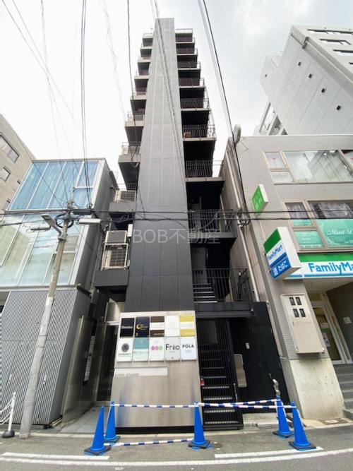 黒く縦に細長い10階建てのビルの外観画像