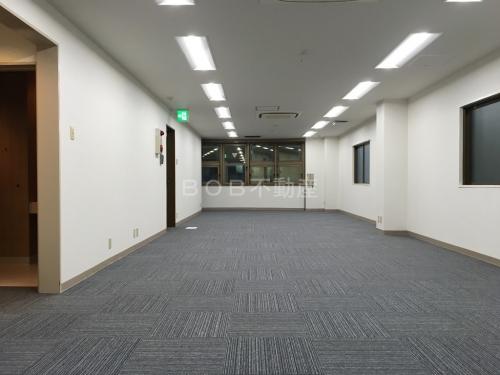 約20坪の白い内装とグレーのタイルカーペット、奥に窓が映った事務所の内装2