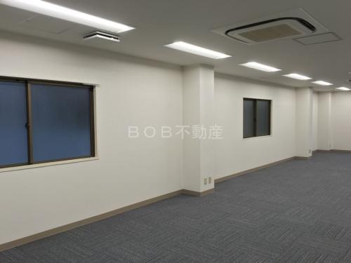 約20坪の白い内装とグレーのタイルカーペット、エアコン、奥に窓が映った事務所の内装