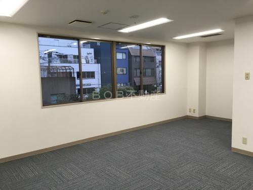 白い内装とグレーのタイルカーペット、窓が映った事務所の内装