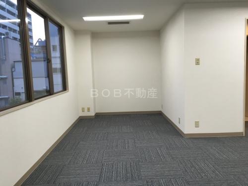 白い内装とグレーのタイルカーペット、窓が映った事務所の内装2